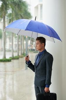 雨の中に傘が付いている通りに立っているアジア系のビジネスマン