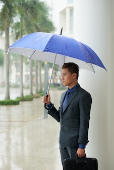 Asian businessman standing in street with umbrella during rain