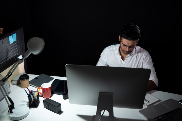 Asian businessman staying overtime late at night working in the office