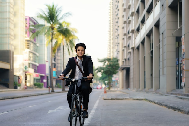 Asian businessman in a suit is riding a bicycle on the city streets for his morning commute to work