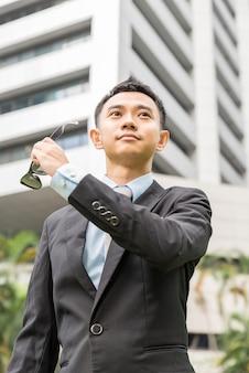 アジアのビジネスマンは彼のサングラスを脱ぐ。男はオフィスビルの外に立っています