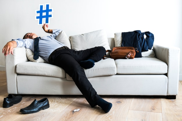 Asian businessman taking break laying on couch