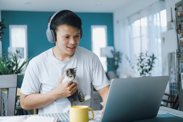 Asian businessman talking to colleague team in video call conference with kitten and smile face. man using computer laptop and headphone for online meeting. smart working from home concept.