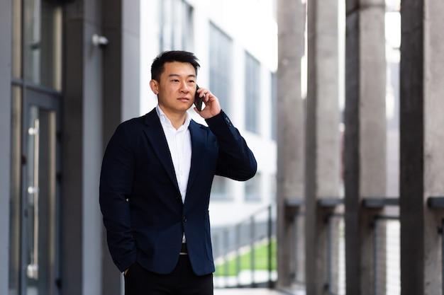 심각한 전화 통화를 하는 아시아 사업가가 화난 대화를 나누고 있다