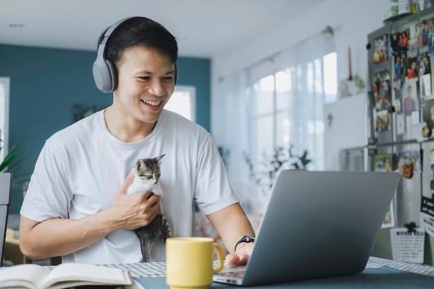 子猫と笑顔でビデオ通話会議で同僚チームと話しているアジアのビジネスマン。オンライン会議にコンピューターのラップトップとヘッドフォンを使用している男性。在宅勤務のスマートコンセプト。