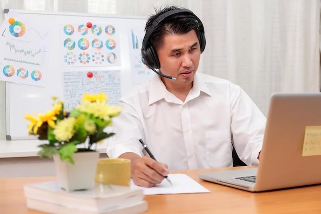 Азиатский бизнесмен разговаривает с командой по видеоконференции, пишет записку на бумаге, деловые люди используют ноутбук и гарнитуру для онлайн-встречи