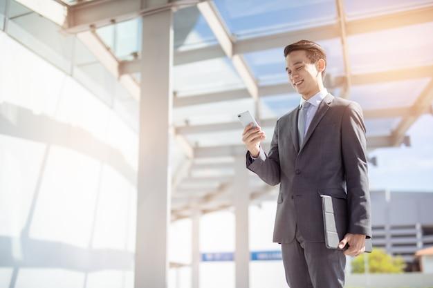 スマートフォンを使用してアジア系のビジネスマン