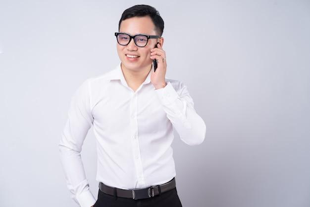 白のスマートフォンを使用してアジアの実業家