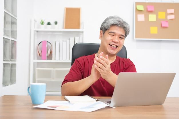 オンライン学習のためのウェブカメラによるラップトップコンピューターの話を呼び出すアジアのビジネスマンのビデオ会議