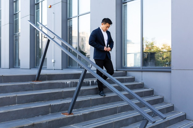 Asian businessman walks up the stairs of the office center, man hurries to a business meeting in a suit