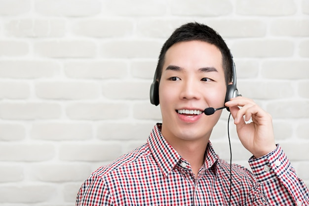 Asian businessman wearing microphone headset as a telemarketing customer service agent, call center job concept