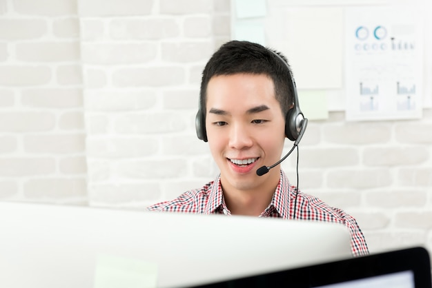 Asian businessman wearing microphone headset working as a telemarketing customer service agent, call center job concept