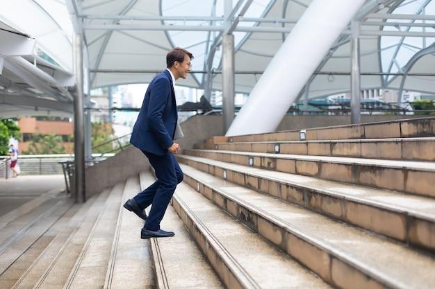 2階で速く走っているスーツのジャケットを着ているアジアのビジネスマンは、朝の屋外で仕事に行きます。