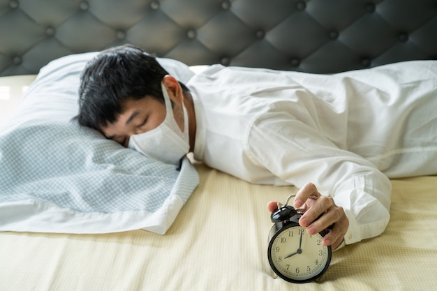 Asian businessman wearing surgical mask sleeping on the bed with alarm clock