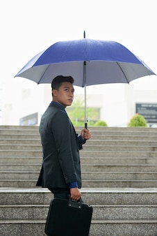 Asian businessman with umbrella and briefcase walking up staircase in rain