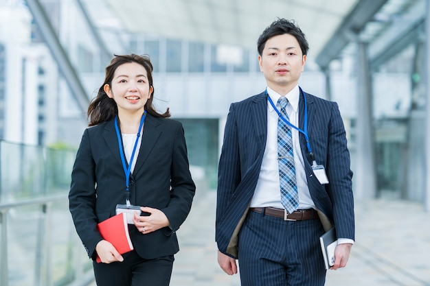 Asian businessman and woman in suits walking side by side