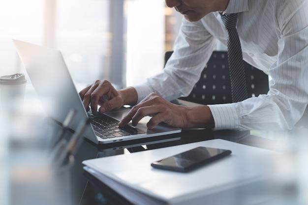オフィスでラップトップコンピューターに取り組んでいるアジアのビジネスマン