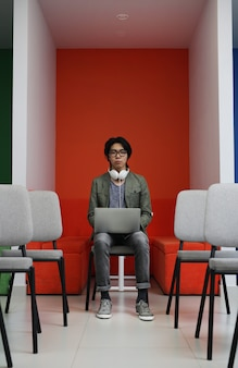 ラップトップに取り組んでいるアジア系のビジネスマン