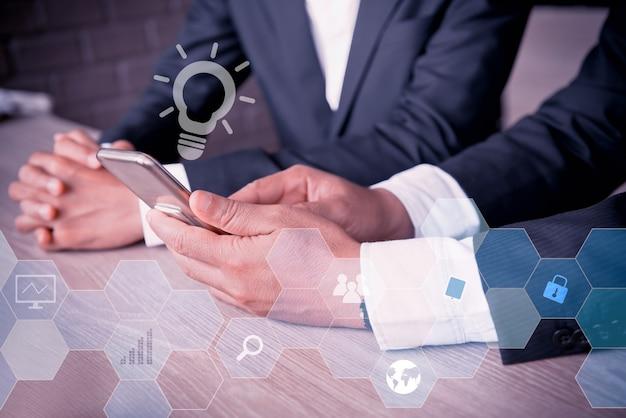 동료 및 팀워크와 함께 스마트폰 작업을 하는 아시아 사업가. 성공적인 비즈니스에 대한 개인 개발을 위한 교육 및 혁신.