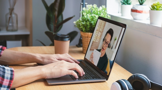 自宅からリモートで作業するアジアのビジネスマンと同僚のビジネスマンとの仮想ビデオ会議会議のウェビナー。ホームオフィスの概念での社会的距離。