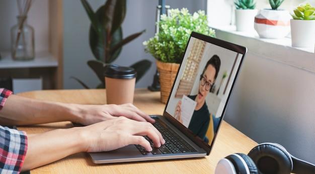 Uomo d'affari asiatico che lavora in remoto da casa e webinar per riunioni di videoconferenza virtuale con colleghi uomini d'affari. distanza sociale a casa concetto di ufficio.