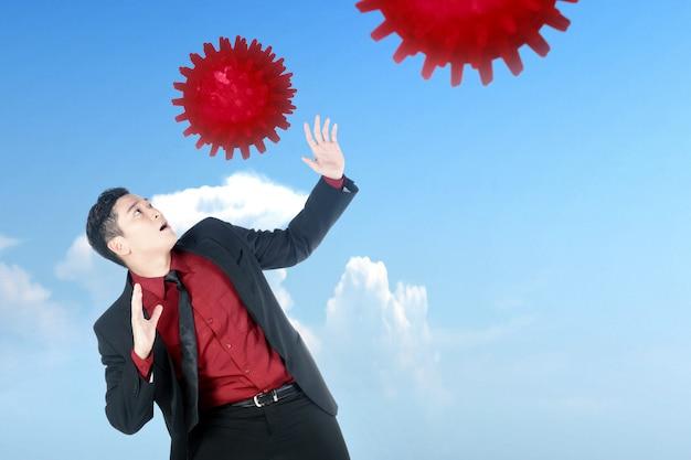コロナウイルスが空気中に広がるのを心配しているアジア系のビジネスマン