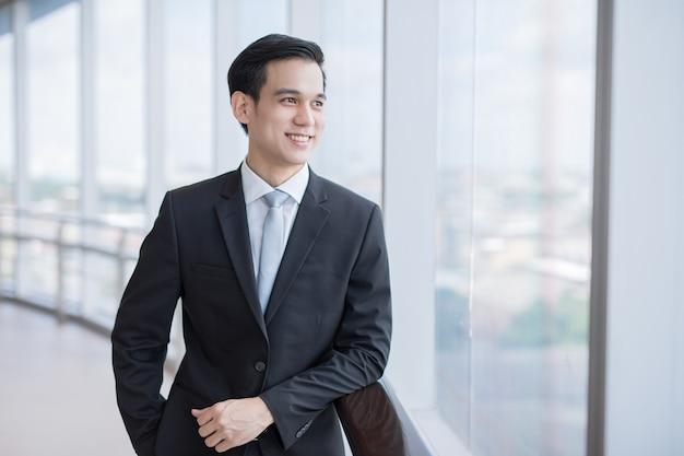 양복을 입은 젊은 아시아 사업가가 회사에서 행복을 베어내고 있다