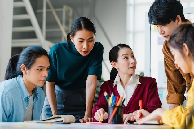 Азиатские бизнесмены и деловые женщины встречают идеи мозгового штурма о приложении для планирования творческого веб-дизайна и разрабатывают макет шаблона для проекта мобильного телефона, работая вместе в небольшом офисе.