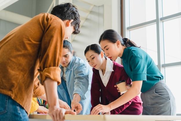 アジアのビジネスマンやビジネスウーマンがクリエイティブなウェブデザイン計画アプリケーションに関するブレーンストーミングのアイデアを会議し、小規模オフィスで一緒に働く携帯電話プロジェクトのテンプレートレイアウトを開発しています。