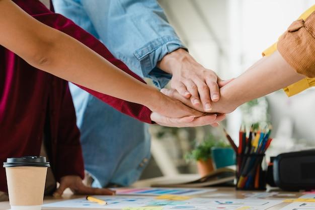 アジアのビジネスマンとビジネスウーマンがブレーンストーミングに出会い、新しいスタートアップに手を挙げて、現代のクリエイティブなオフィスで一緒に働くモチベーションを強めています。同僚のチームワークの概念。