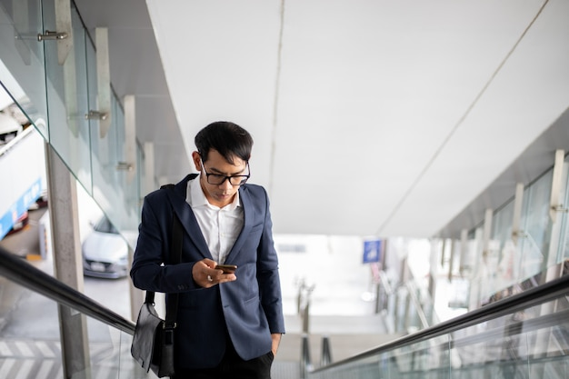 Asian businessmen are using their phones and going up the escalator to work in the morning.