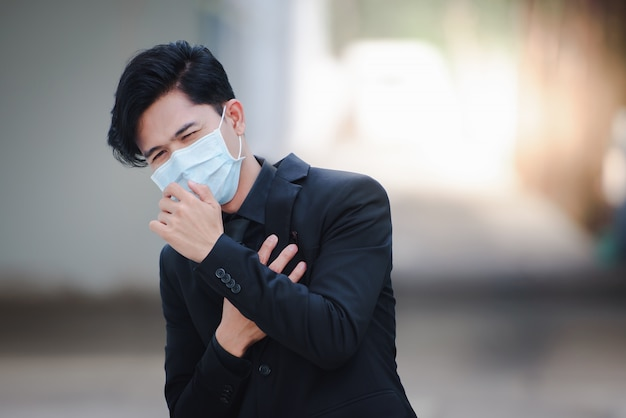 Asian businessmen look good, are sick, and wear masks. the rapid spread of the new coronavirus by birth in wuhan, china.