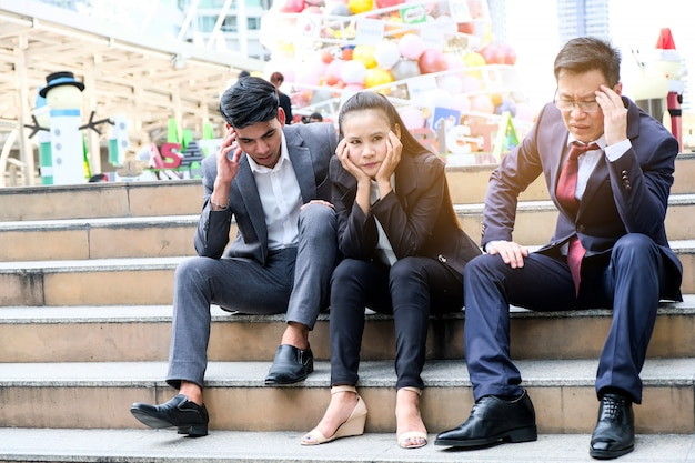 Asian businessmen sitting dismal because of unemployment.