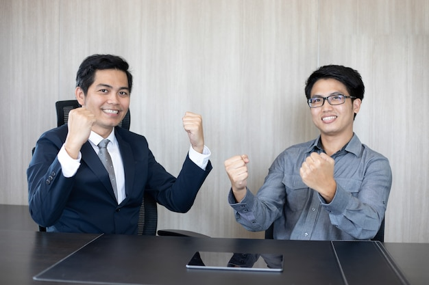Asian businessmen success and winning concept - happy team with raised up hands celebrating the breakthrough and achievements