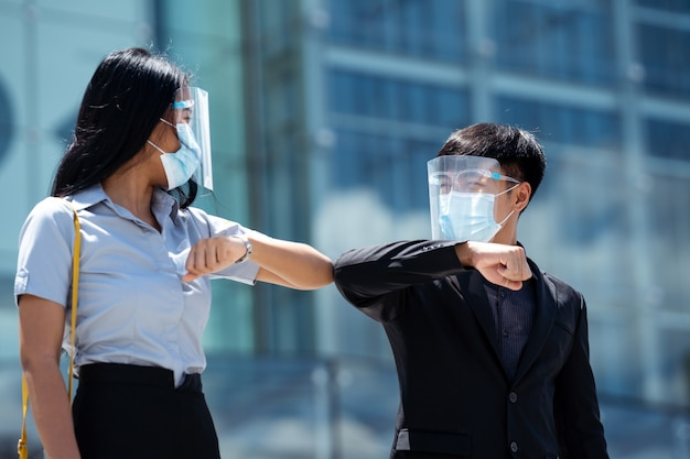 Asian businessmen use elbows to greet each other. they wear face shields.