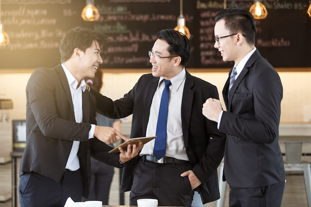 Asian businessmen using a tablet for business and discussing ideas at meeting