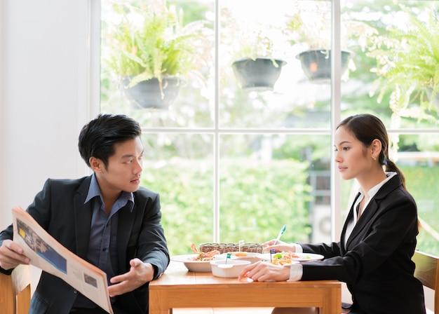 アジアのビジネスマンは、レストランで昼食を取るために休憩中です。新聞を読んでいる男性のレストラン。