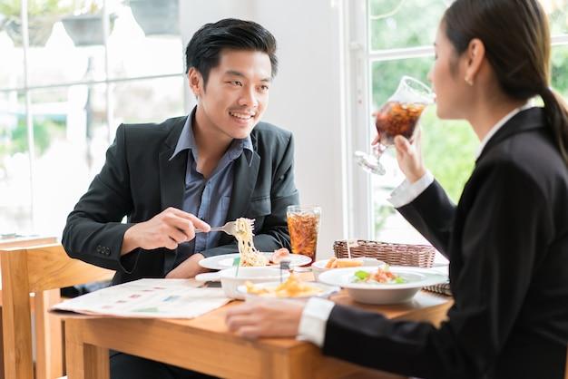アジアのビジネスマンがレストランでのランチ休憩中