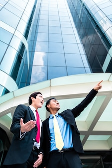 Asian businesspeople in front of high rise building