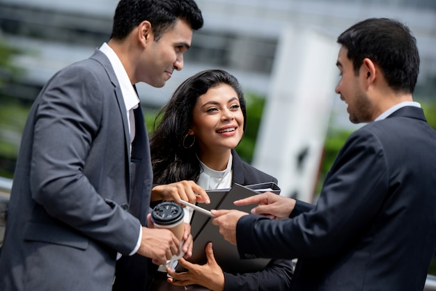 Asian businesspeople having outside office meeting