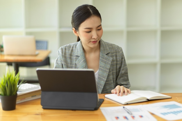 Asian businesswoman analysing statistics on  tablet working with financial graphs charts reports