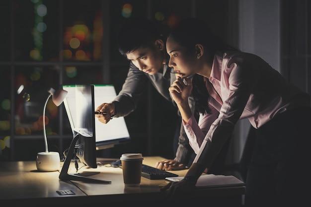 사무실에서 기술 컴퓨터와 함께 늦게까지 열심히 일하는 아시아 사업가 및 사업가