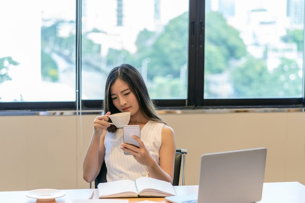 Asian businesswoman in casual suit are glad when completed doing online shopping