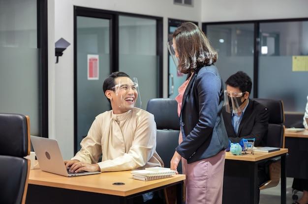 현대 사무실에서 책상에 얼굴 방패를 입고 행복하고 웃는 게이 동료와 컨설팅 아시아 사업가