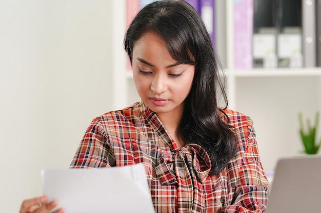 아시아 사업가 사무실에서 그녀의 직장에서 비즈니스 서류에 초점을 맞추고 있습니다. 재무 보고서 개념 분석.