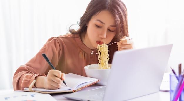 アジアの実業家は仕事中に麺を食べなければなりません