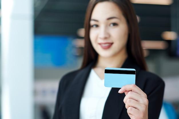 Азиатская коммерсантка держа пустую кредитную карточку. портрет красивой девушки в офисе или конференц-зале