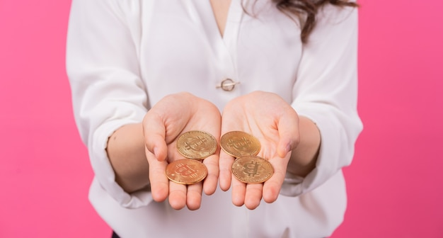 彼女の手でビットコインを保持しているアジアの実業家