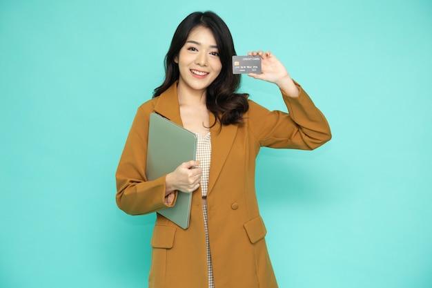 컴퓨터 노트북을 들고 신용 카드를 보여주는 아시아 여성
