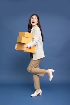 파란색 배경에 고립 된 패키지 소포 상자를 들고 아시아 사업가